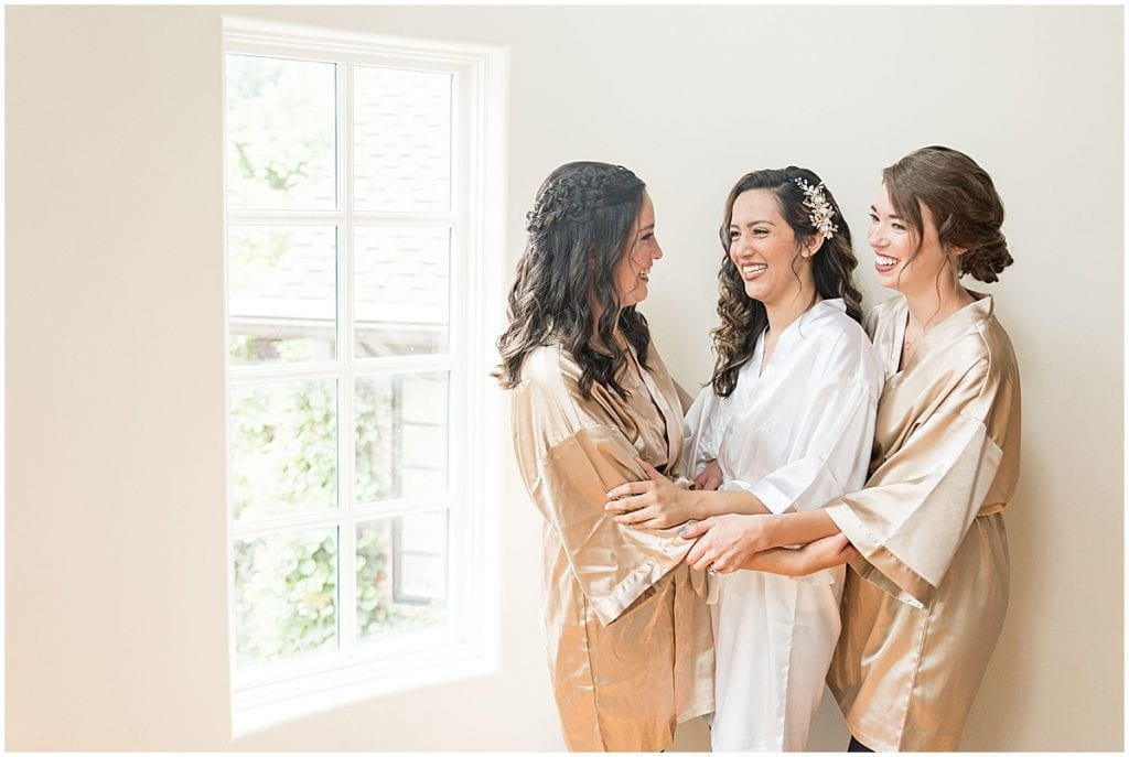Bride and her bridesmaids laughing and getting ready for the wedding.