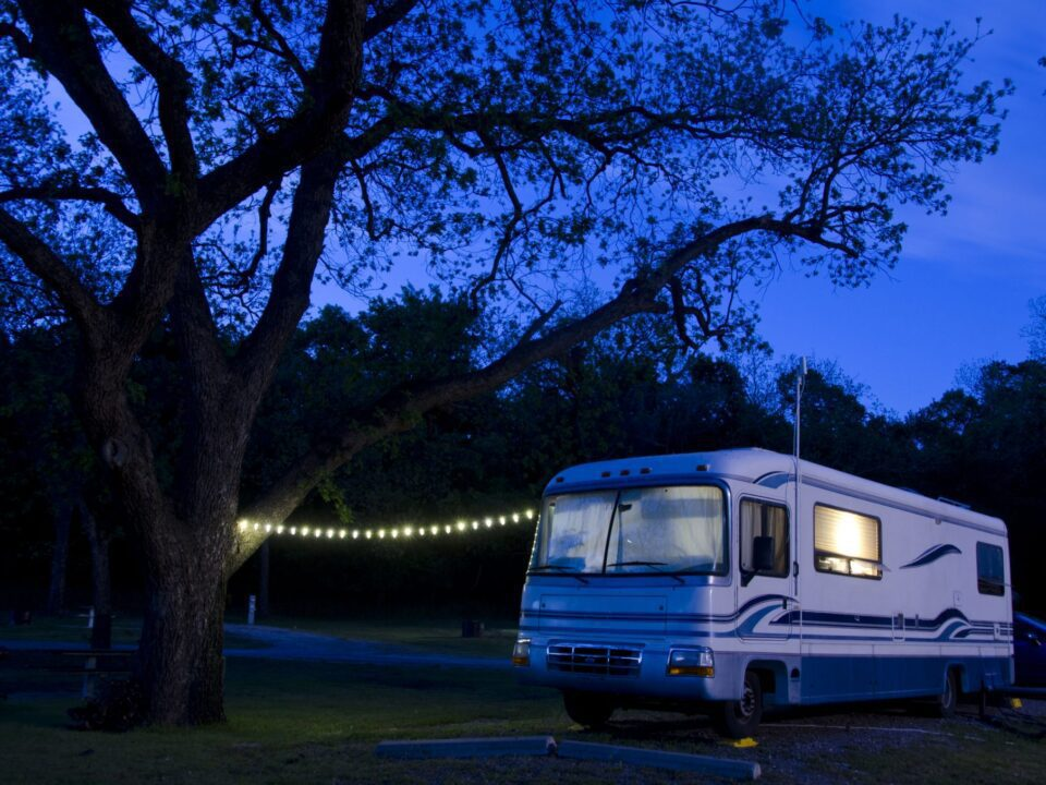 an RV with interior lights on and an exterior string of lights during the night