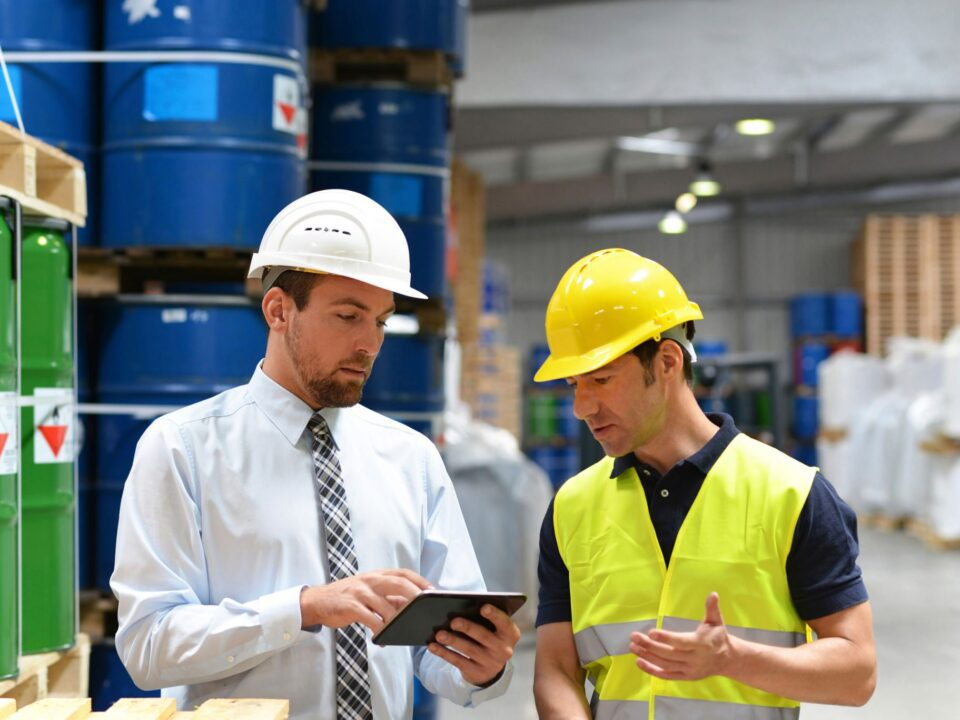 two men wearing hard hats in a manufacturing warehouse